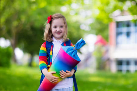 day of school: Happy child holding traditional German candy cone on the first school day. Little student with backpack and books excited to be back to school. Beginning of class in Germany with sweets for kids. Stock Photo