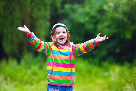 rain weather: Little girl playing in rainy summer park. Child with rainbow umbrella, waterproof coat and boots jumping in puddle in the rain. Kid walking in autumn shower. Outdoor fun by any weather
