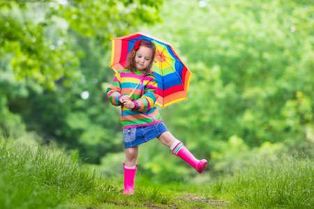 Spelen van het meisje in de regenachtige zomer park. Kind met rainbow paraplu, waterdichte jas en laarzen springen in plas in de regen. Kid wandelen in de herfst douche. Outdoor plezier door alle weersomstandigheden