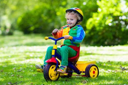 Netter Junge mit Schutzhelm seinem Dreirad im sonnigen Sommerpark fahren. Kinder fahren Fahrrad. Erstes Bike für kleines Kind. Aktive Kleinkind Kind spielen und Radfahren im Freien. Kinder spielen im Garten. Standard-Bild