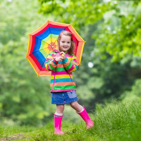 Spelen van het meisje in de regenachtige zomer park. Kind met rainbow paraplu, waterdichte jas en laarzen springen in plas in de regen. Kid wandelen in de herfst douche. Outdoor plezier door alle weersomstandigheden Stockfoto