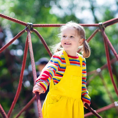 niños rubios: niño activo que juega en la red de escalada y el salto en el trampolín en el patio patio de la escuela. Los niños juegan y suben al aire libre en un día soleado de verano. linda chica en el columpio nido en el centro deporte preescolar.