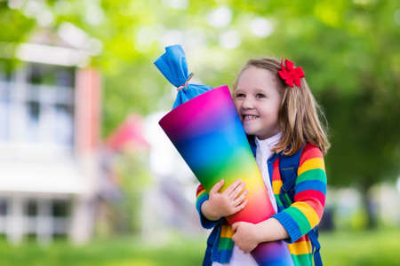 Happy child holding traditional German candy cone on the first school day. Little student with backpack and books excited to be back to school. Beginning of class in Germany with sweets for kids. Stock Photo