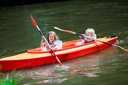 preschoolers: Family on kayak and canoe tour. Two little kids paddling in kayaks in a river on a sunny day. Children in summer sport camp. Active preschoolers kayaking in a lake. Water fun during school vacation.
