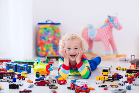 for children toys: Funny curly toddler boy playing with his model car collection on the floor. Transportation and rescue toys for children. Toy mess in child room. Many cars for little boys. Educational games for kids. Stock Photo