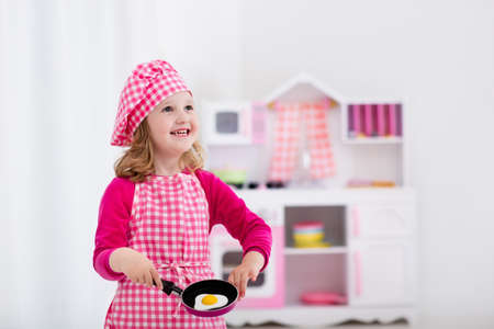 for children toys: Little girl in chef hat and apron cooking fried eggs in toy kitchen.  Wooden toys for young children. Kids play and cook at home or daycare. Toddler kid playing with stove, tableware, pans and dishes.