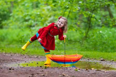 personas saltando: Niña que juega en el parque de verano lluvioso. Niño con paraguas de colores del arco iris, capa impermeable y botas salta en el charco en la lluvia. Kid pie en la ducha otoño. diversión al aire libre por cualquier clima Foto de archivo