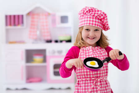 Little girl in chef hat and apron cooking fried eggs in toy kitchen.  Wooden toys for young children. Kids play and cook at home or daycare. Toddler kid playing with stove, tableware, pans and dishes.
