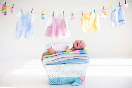 kids wear: Newborn baby on a pile of clean dry towels. New born child after bath in a towel. Family washing clothes. Kids wear hanging on a line. Infant apparel, textile for children. Smiling boy after shower. Stock Photo
