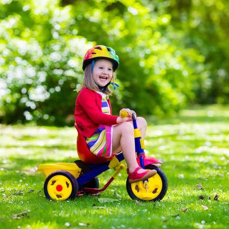 Nettes Mädchen mit Schutzhelm ihrem Dreirad im sonnigen Sommerpark fahren. Kinder fahren Fahrrad. Erstes Bike für kleines Kind. Aktive Kleinkind Kind spielen und Radfahren im Freien. Kinder spielen im Garten.