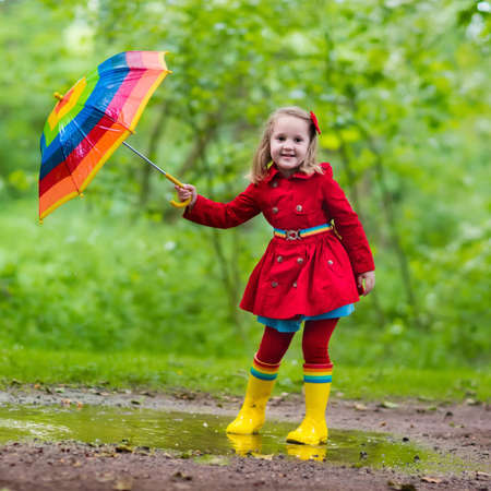 rain weather: Little girl playing in rainy summer park. Child with colorful rainbow umbrella, waterproof coat and boots jumping in puddle in the rain. Kid walking in autumn shower. Outdoor fun by any weather