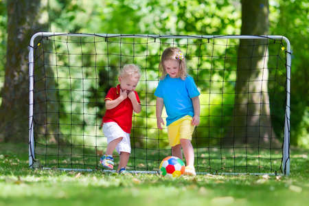 attacker: Two happy children playing European football outdoors in school yard. Kids play soccer. Active sport for preschool child. Ball game for young kid team. Boy and girl score a goal in football match.