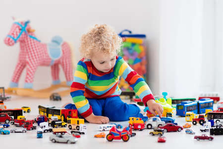 boys toys: Funny curly toddler boy playing with his model car collection on the floor. Transportation and rescue toys for children. Toy mess in child room. Many cars for little boys. Educational games for kids. Stock Photo