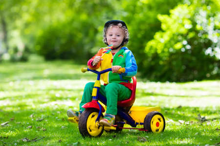 toddler boy: Cute boy wearing safety helmet riding his tricycle in sunny summer park. Kids ride bicycle. First bike for little child. Active toddler kid playing and cycling outdoors. Kids play in the garden. Stock Photo