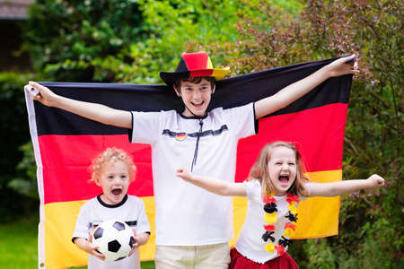 Children cheering and supporting German national football team. Kids fans and supporters of Germany during soccer championship. Family with teenager boy, little girl and baby watch football game.