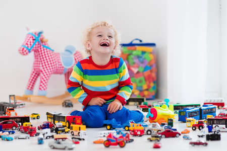 toddler boy: Funny curly toddler boy playing with his model car collection on the floor. Transportation and rescue toys for children. Toy mess in child room. Many cars for little boys. Educational games for kids. Stock Photo
