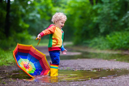 Little boy playing in rainy summer park. Child with colorful rainbow umbrella, waterproof coat and boots jumping in puddle and mud in the rain. Kid walking in autumn shower. Outdoor fun by any weather Stock Photo