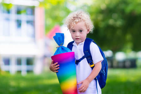 beginning: Happy child holding traditional German candy cone on the first school day. Little student with backpack and books excited to be back to school. Beginning of class in Germany with sweets for kids. Stock Photo
