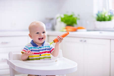 solid food: Happy baby sitting in high chair eating carrot in a white kitchen. Healthy nutrition for kids. Bio carrot as first solid food for infant. Children eat vegetables. Little boy biting raw vegetable. Stock Photo