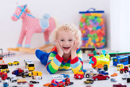 kids toys: Funny curly toddler boy playing with his model car collection on the floor. Transportation and rescue toys for children. Toy mess in child room. Many cars for little boys. Educational games for kids. Stock Photo