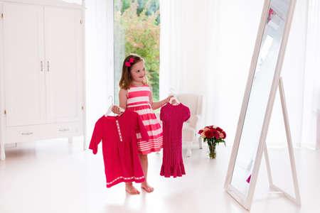 niños vistiendose: Niña elección de vestidos en el dormitorio blanco. Niño que mira la reflexión de espejo celebración de traje de color rosa vestido de elección. vivero niñas. Compras de ropa para niños. Interior vestidor para los niños. Foto de archivo