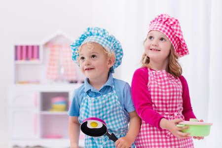 cocineros: Niña y niño en sombrero del cocinero y un delantal para cocinar huevos fritos en la cocina de juguete. juguetes de madera para niños pequeños. Los niños juegan y cocinar en casa o en la guardería. niño niño que juega con estufa, sartenes y platos. Foto de archivo