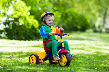 niños en bicicleta: chico lindo que lleva el casco de seguridad montado en su triciclo en el parque soleado de verano. Niños andar en bicicleta. En primer lugar bicicleta para niño pequeño. Activo niño jugando niño y montar en bicicleta al aire libre. Los niños juegan en el jardín. Foto de archivo