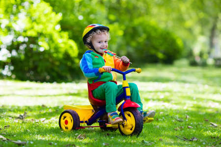 Cute boy wearing safety helmet riding his tricycle in sunny summer park. Kids ride bicycle. First bike for little child. Active toddler kid playing and cycling outdoors. Kids play in the garden. Stock Photo