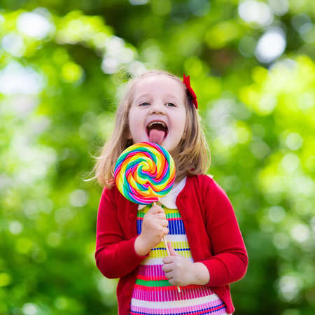 sweet tooth: Cute little girl with big colorful lollipop. Child eating sweet candy bar. Sweets for young kids. Summer outdoor fun. Preschooler kid with sugar lolly. Children having snack in a park after preschool.