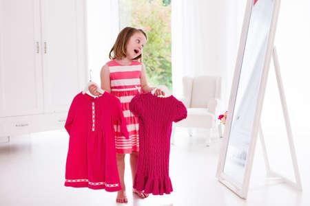 preschooler: Little girl choosing dresses in white bedroom. Child watching mirror reflection holding pink dress choosing outfit. Girls nursery.  Shopping clothing for kids. Dressing room interior for children.