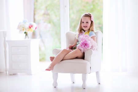 Little girl smelling peony flower bouquet sitting in a white chair in sunny bedroom. Nursery interior with flowers for girls. Child ready for birthday party holding pink peonies. Kids play room.