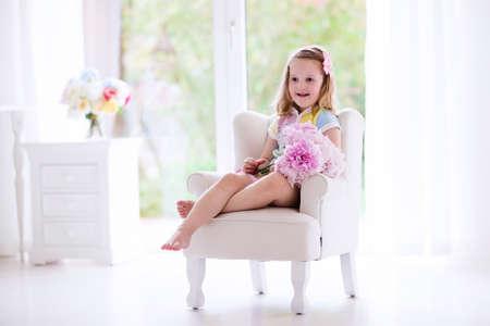 rocker girl: Niña olor ramo de flores de peonía sentado en una silla blanca en el dormitorio soleado. entre vivero con flores para las niñas. Niño listo para la celebración de la fiesta de cumpleaños peonías rosas. Los niños juegan ambiente.
