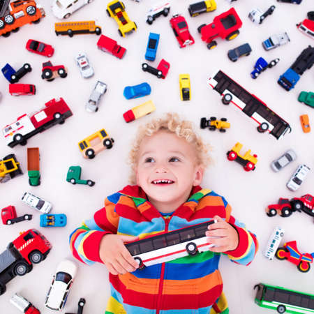 mess: Funny curly toddler boy playing with his model car collection lying on the floor. Transportation and rescue toys for children. Toy mess in kids room. View from above. Many cars for little boys.