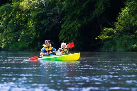 piragua: Familia en kayaks y paseo en canoa. Padre e hijo remar en kayak en un río en un día soleado. Los niños en el campo de deportes de verano. kayak preescolar activo en un lago. diversión en el agua durante las vacaciones escolares.