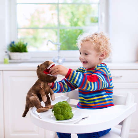 solid food: Happy little boy in high chair eating broccoli and feeding his toy dinosaur in a white kitchen. Healthy nutrition for kids and baby. Bio vegetable as solid food for infant. Children eat vegetables.