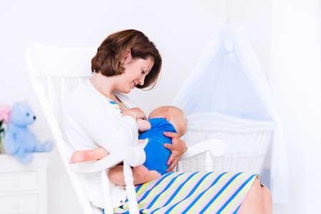 Junge Mutter mit ihrem neugeborenen Kind. Mom Baby-Pflege. Frau und neugeborene Junge im weißen Schlafzimmer mit Schaukelstuhl und blau Krippe. Nursery inter. Mutter spielt mit Kind lachen. Familie zu Hause