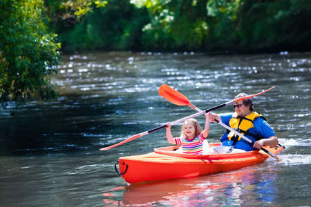 family vacation: Family on kayaks and canoe tour. Father and child paddling in kayak in a river on a sunny day. Children in summer sport camp. Active preschooler kayaking in a lake. Water fun during school vacation. Stock Photo