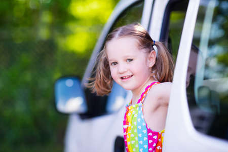mini: Little girl with funny pigtails watching out of car window sitting on front driver seat during a break on a family vacation road trip on summer day. Child in white minivan. Traveling by car with kids.