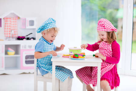 Little girl and boy in chef hat and apron cooking in toy kitchen. Educational toys for young children. Kids play, cut wooden vegetables and cook. Toddler kid playing with stove, pans and dishes. Stock Photo