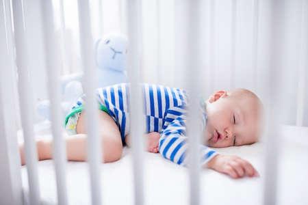 Slapende baby en zijn speelgoed in witte wieg. Nursery inter en beddengoed voor kinderen. Schattige kleine jongen slapen in de wieg. Kid een dutje in witte slaapkamer. Gezond kind in bodysuit pyjama.