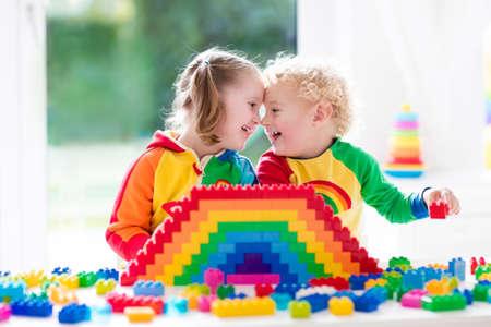 gemelos niÑo y niÑa: Niño jugando con juguetes de colores. Niña y divertida bebé rizado con bloques de juguete educativos. Los niños juegan en la guardería o al preescolar. Desorden en la habitación de los niños. Los niños pequeños a construir una torre en el jardín de infantes.