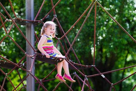 mignonne petite fille: Actif petit enfant jouant sur l'escalade filet et sauter sur le trampoline au cour de l'école aire de jeux. Les enfants jouent et grimpent à l'extérieur le jour d'été ensoleillé. Cute girl sur la balançoire nid au centre sportif préscolaire.