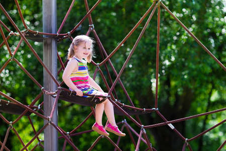 cute little girl: Active little child playing on climbing net and jumping on trampoline at school yard playground. Kids play and climb outdoors on sunny summer day. Cute girl on nest swing at preschool sport center. Stock Photo