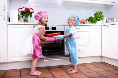cocineros: Niño pequeño y chica, hermano y hermana hornear delicioso pastel de manzana en la cocina blanca. Los niños que toman pastel de frutas fuera del horno. Niños hornear en casa. niño del niño y el niño en edad preescolar cocinar para la familia. Foto de archivo
