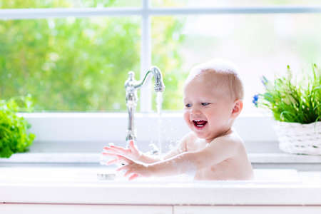 Baby taking bath in kitchen sink. Child playing with foam and soap bubbles in sunny bathroom with window. Little boy bathing. Water fun for kids. Hygiene and skin care for children. Bath room interior Imagens