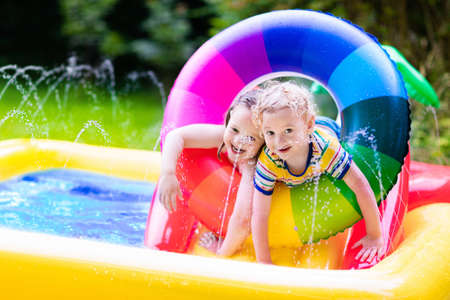 Children playing in inflatable baby pool. Kids swim and splash in colorful garden play center. Happy boy and girl playing with water toys on hot summer day. Family having fun outdoors in the backyard. Фото со стока