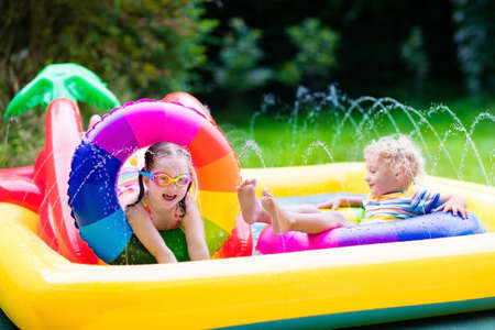 Children playing in inflatable baby pool. Kids swim and splash in colorful garden play center. Happy boy and girl playing with water toys on hot summer day. Family having fun outdoors in the backyard. Stock Photo