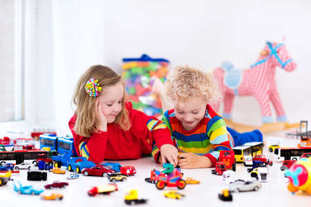 kids toys: Little toddler boy and girl playing with model car collection on the floor. Transportation and rescue toys for children. Toy mess in child room. Many cars for little boys. Educational games for kids.