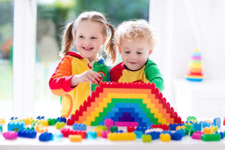 Child playing with colorful toys. Little girl and funny curly baby boy with educational toy blocks. Children play at day care or preschool. Mess in kids room. Toddlers build a tower in kindergarten. Stock Photo