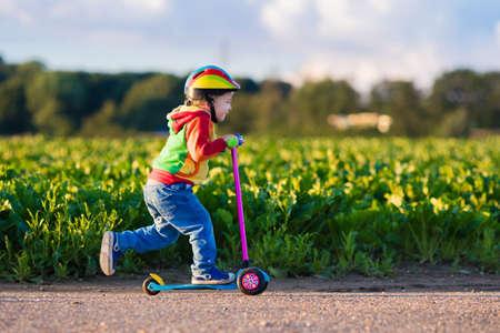 日当たりの良い夏の日に都市公園でスクーターに乗ることを学んでいる小さな子供。ローラーに乗って安全ヘルメットでかわいい幼児少年。外で遊ぶ子供たち。アクティブなレジャーと子供たちのためのアウトドア スポーツ。 写真素材 - 59308868